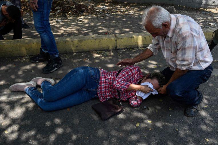 Een vrouw ligt bedwelmd door traangas op straat. Beeld AFP