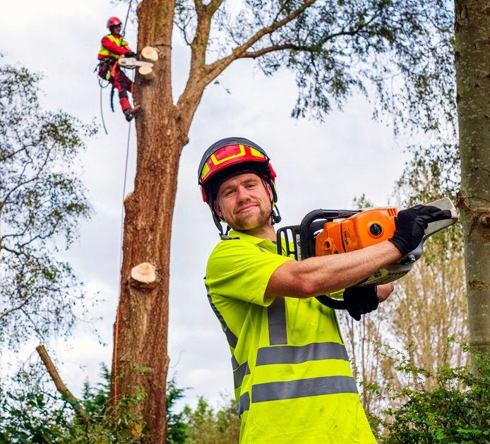 Boomverzorger Mike Ubbink (29, Ter Aar) met boomzaag. Op de achtergrond zijn collega Julian Menkema uit Alphen aan den Rijn.