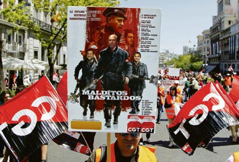 Tijdens een demonstratie van de grootste Spaanse vakbond in mei werden op een filmposter van Tarantino's Inglourious Basterds de acteurs vervangen door Spaanse politici. (FOTO REUTERS) Beeld REUTERS