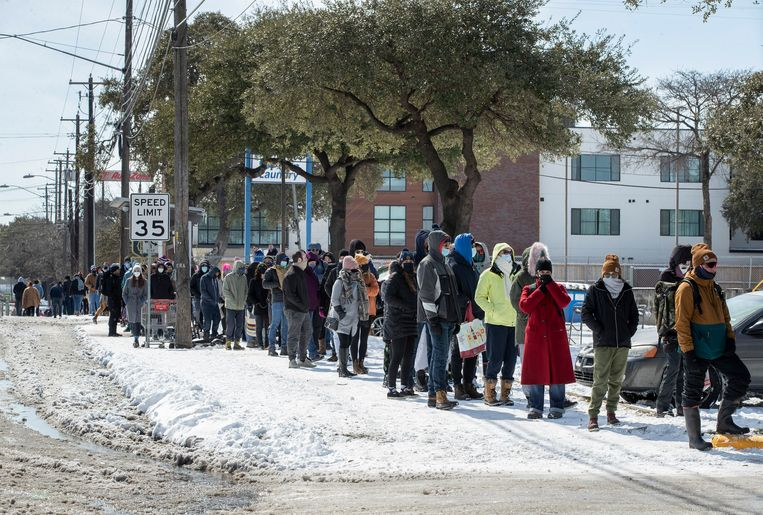 Mensen staan buiten in de kou in de rij om boodschappen te gaan doen. Beeld AP