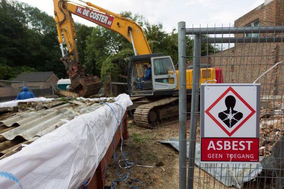 Een bordje waarschuwt voor het asbestgevaar op een bouwwerf.