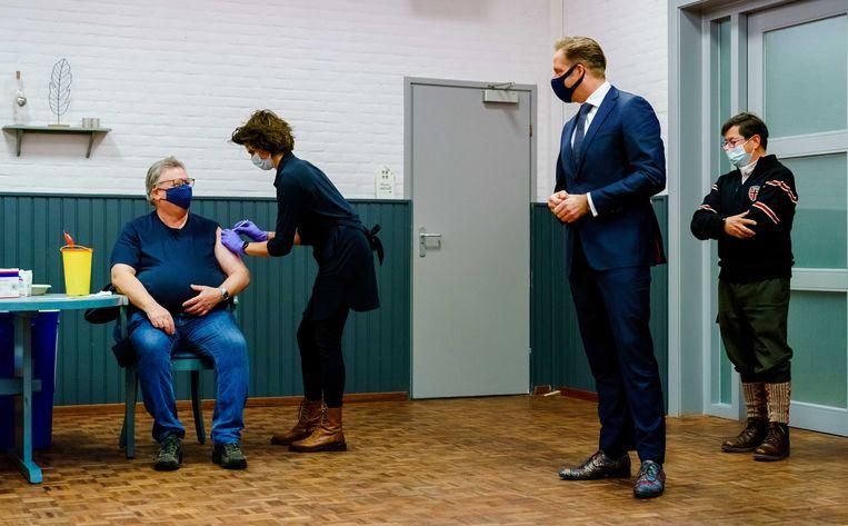 Demissionair minister Hugo de Jonge kijkt naar een huisarts uit Bruinisse die een patiënt prikt met het AstraZenecavaccin.  Beeld EPA