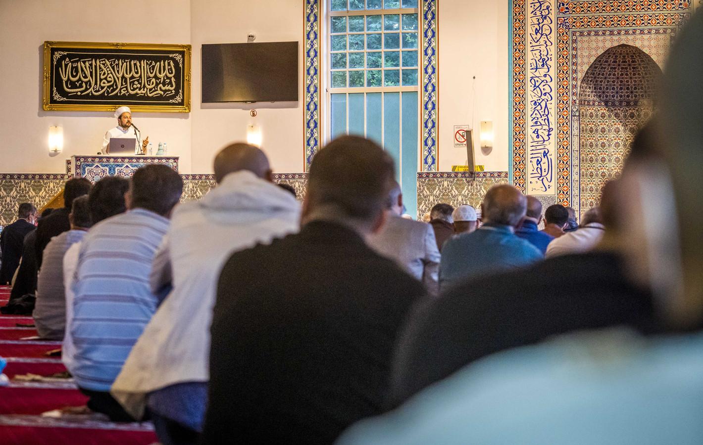 Moslims tijdens het ochtendgebed in de Mevlana Moskee. Hier wordt de eerste dag van het belangrijkste feest van de islam, het Offerfeest, gevierd. Door de coronacrisis is de anderhalve meter afstand nog steeds van kracht voor samenscholingen.