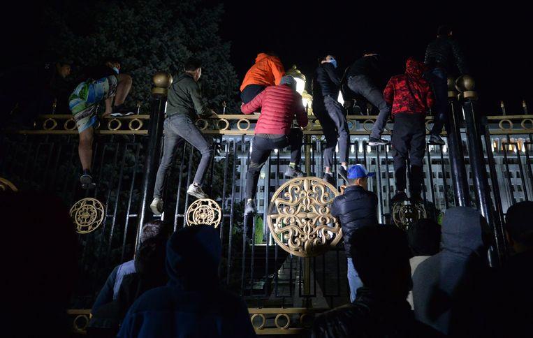 Demonstranten beklimmen de hekken rond het parlement in de hoofdstad Bisjkek.  Beeld AFP