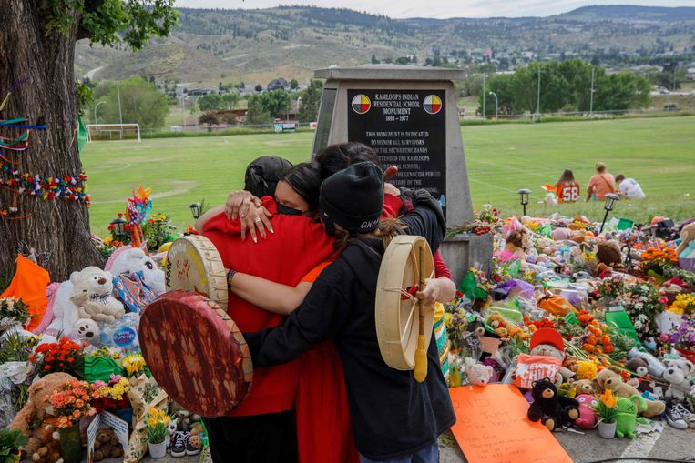 Rouwende leden van de Mosakahiken Cree Nation hug bij een herdenkplek nabij de voormalige Kamloops missieschool,  waar de stoffelijke overschotten van 215 kinderen zijn gevonden. Beeld AFP