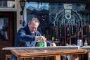 Joep Blokland bezig met onderhoud / schilderwerk aan het terras van zijn café. Hij doet niet mee aan de protestactie.