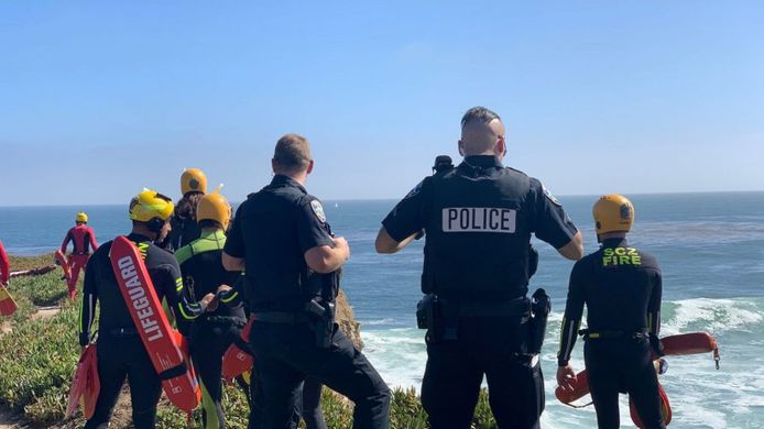 Politieagenten kijken over de rand van de klif naar de gecrashte autodief.