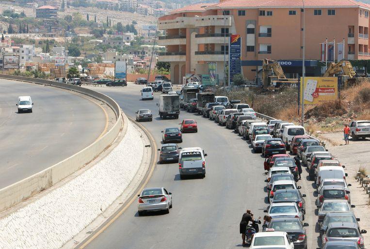 Een lange rij auto's staat te wachten voor een tankstation in Jiyeh. Politie patrouilleert regelmatig bij de pompen, ter voorkoming van vechtpartijen.  Beeld Reuters