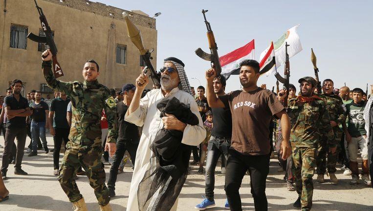 Vrijwilligers tonen hun wapens in een optocht door Sadr City, een wijk van Bagdad. Beeld REUTERS