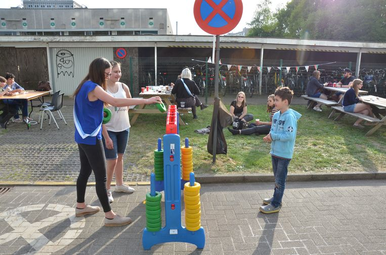 Studenten en kinderen uit de buurt spelen samen een spelletje vier-op-een-rij.
