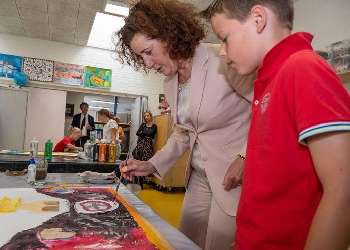 Minister Ingrid van Engelshoven helpt op basisschool 't Klinket Hugo Wouters uit groep 8 met zijn schilderij.