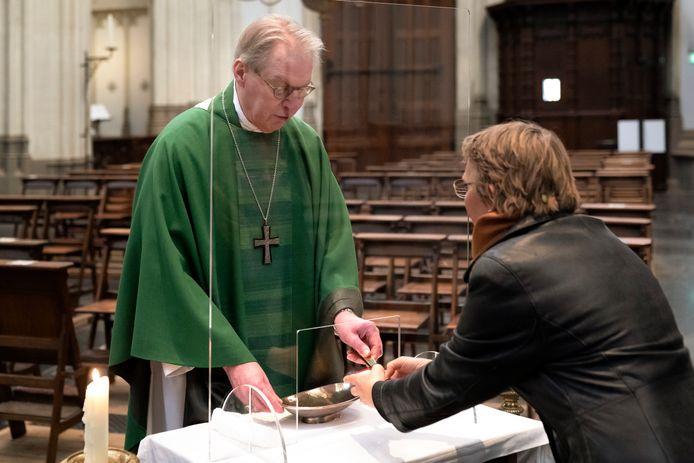 De Bossche bisschop Gerard de Korte reikt in de Sint-Jan volgens de richtlijn de hostie uit vanachter een hoestscherm.