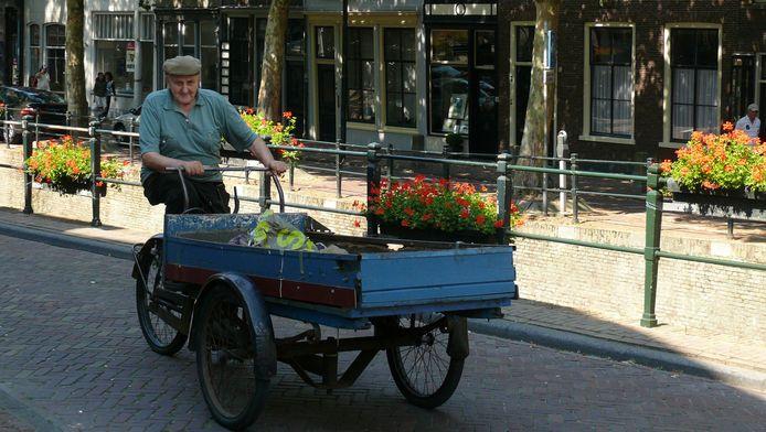 Willem van Roijen met zijn oude vertrouwde bakfiets in Gouda, waar hij oud ijzer ophaalde.