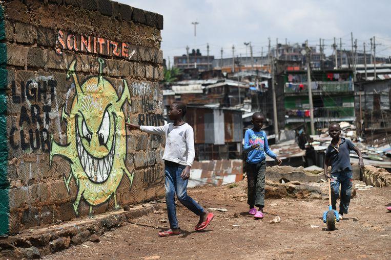Jongens bij een muurschildering in de sloppenwijk Mathare in Nairobi. Beeld AFP