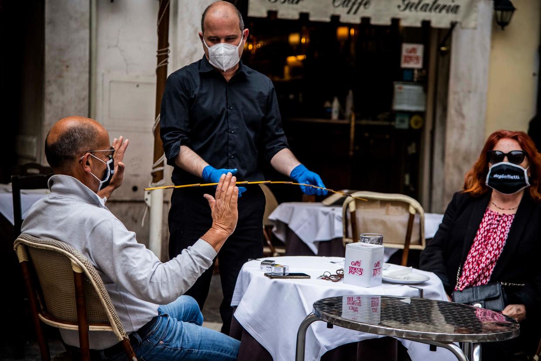 Een café in Rome dat weer openging, met de verplichte afstand tussen de bezoekers. Beeld Photo News