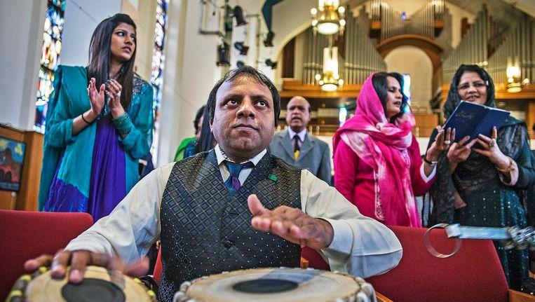 Leden van de Urdu-gemeenschap komen in Amsterdam bijeen voor een dienst. De Pakistaanse christenen zijn als buitengewone gemeente in de Protestantse Kerk in Nederland opgenomen. Beeld  Guus Dubbelman / de Volkskrant