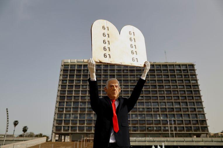 Een beeld van de Israëlische premier Benjamin Netanyahu in Tel Aviv met het getal 61, een verwijzing naar de parlementaire meerderheid die nodig is om een regering te vormen.  Beeld Reuters