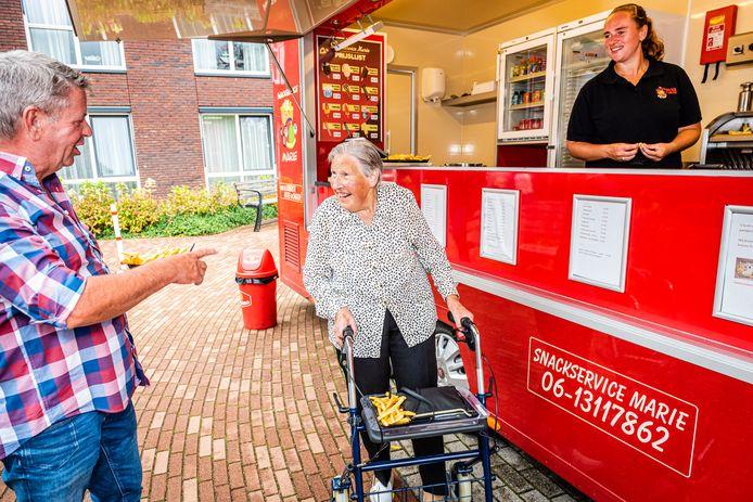 Dirk Koeleman trakteert de bewoners van de Aarhoeve op friet. Samen met mevrouw Riet de Wit wacht hij bij de frietkraam van Mariëlle van der Hoorn en haar moeder Elly op zijn patatjes.