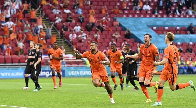 Wout Weghorst en Frenkie de Jong (rechts) lopen juichend op Memphis Depay af, nadat hij Nederland uit een strafschop op een 1-0 voorsprong heeft gebracht. Beeld EPA