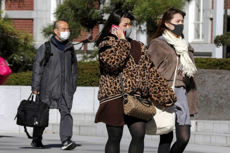 Mensen met mondmaskers in Tokio. In de zomer vinden daar normaal gezien de Olympische Spelen plaats, maar de kans wordt steeds groter dat het evenement uitgesteld zal moeten worden.