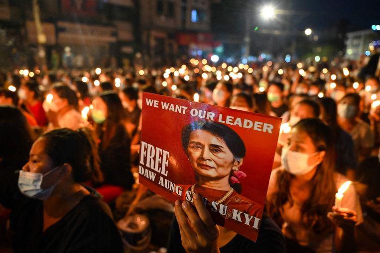 Een demonstrant met een afbeelding van Aung San Suu Kyi tijdens een protest tegen de coup in Yangon. Beeld AFP