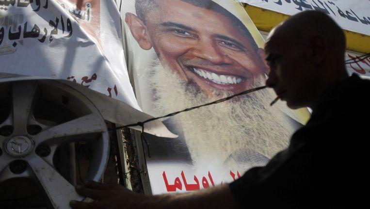 Een demonstrant hangt posters op van Obama met lange baard, om een statement te maken tegen de relatie tussen de VS en Egypte. Beeld REUTERS