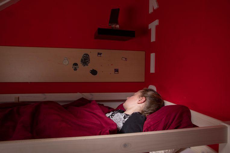 ... Curtis luistert via de smartphone boven zijn hoofd terwijl hij in bed ligt. Beeld Martijn Gijsbertsen