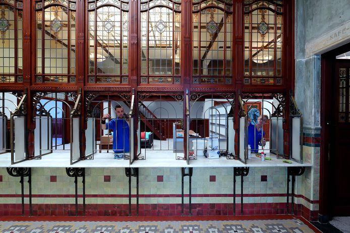 De koperen tralies van de beroemde loketten van de bank van Luykx en later Van Lanschot worden opgepoetst.