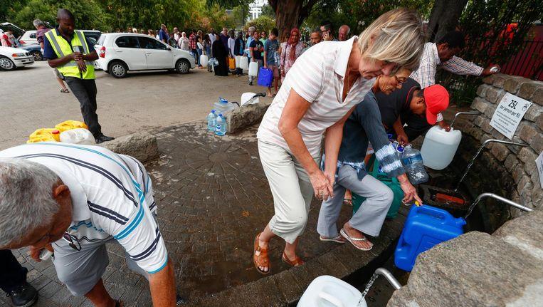 Inwoners van Kaapstad tappen water bij een bron Beeld epa