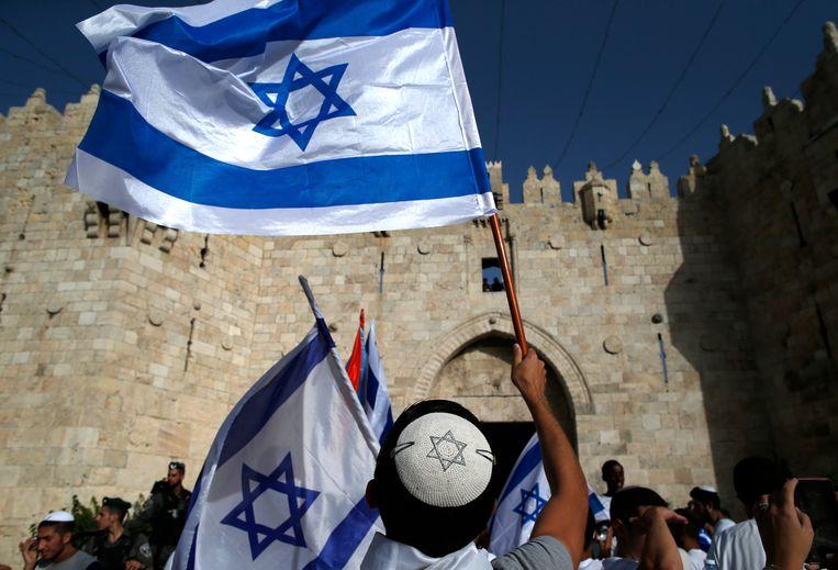 Jongeren stappen op in de Jom Jerusalayim-parade, die de 'hereniging' van Jeruzalem viert na de Zesdaagse Oorlog. Beeld AFP