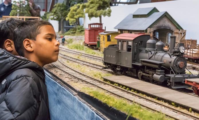 Kinderen volgen de gang van een oude locomotief tijdens een modelspoorshow in Amsterdam.
