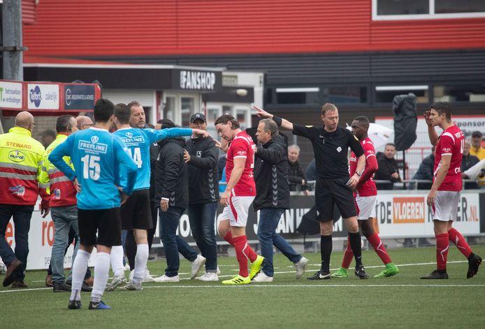 Lars Middelwijk (links, rode shirt) moet nog drie wedstrijden toekijken bij DOVO.