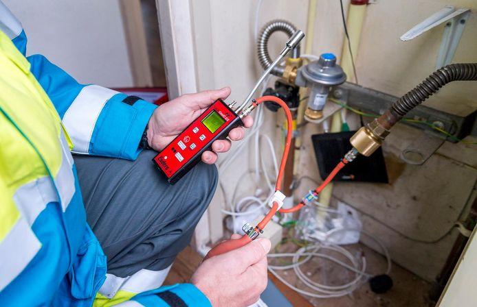 Een monteur controleert de gasleiding voorafgaand aan het plaatsen van een slimme gasmeter.
