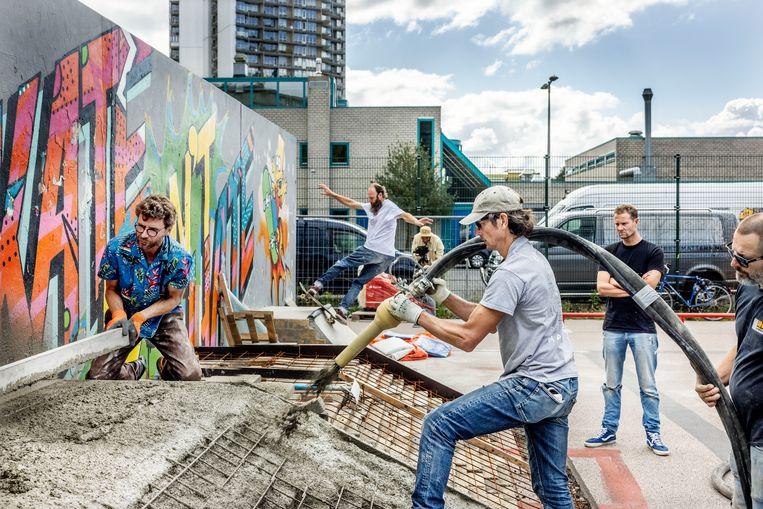 Vrijwilligers storten beton voor het skaepark in Zuidoost. 'Het dingen zelf doen hoort wel echt bij de skatecultuur.' Beeld Jean-Pierre Jans