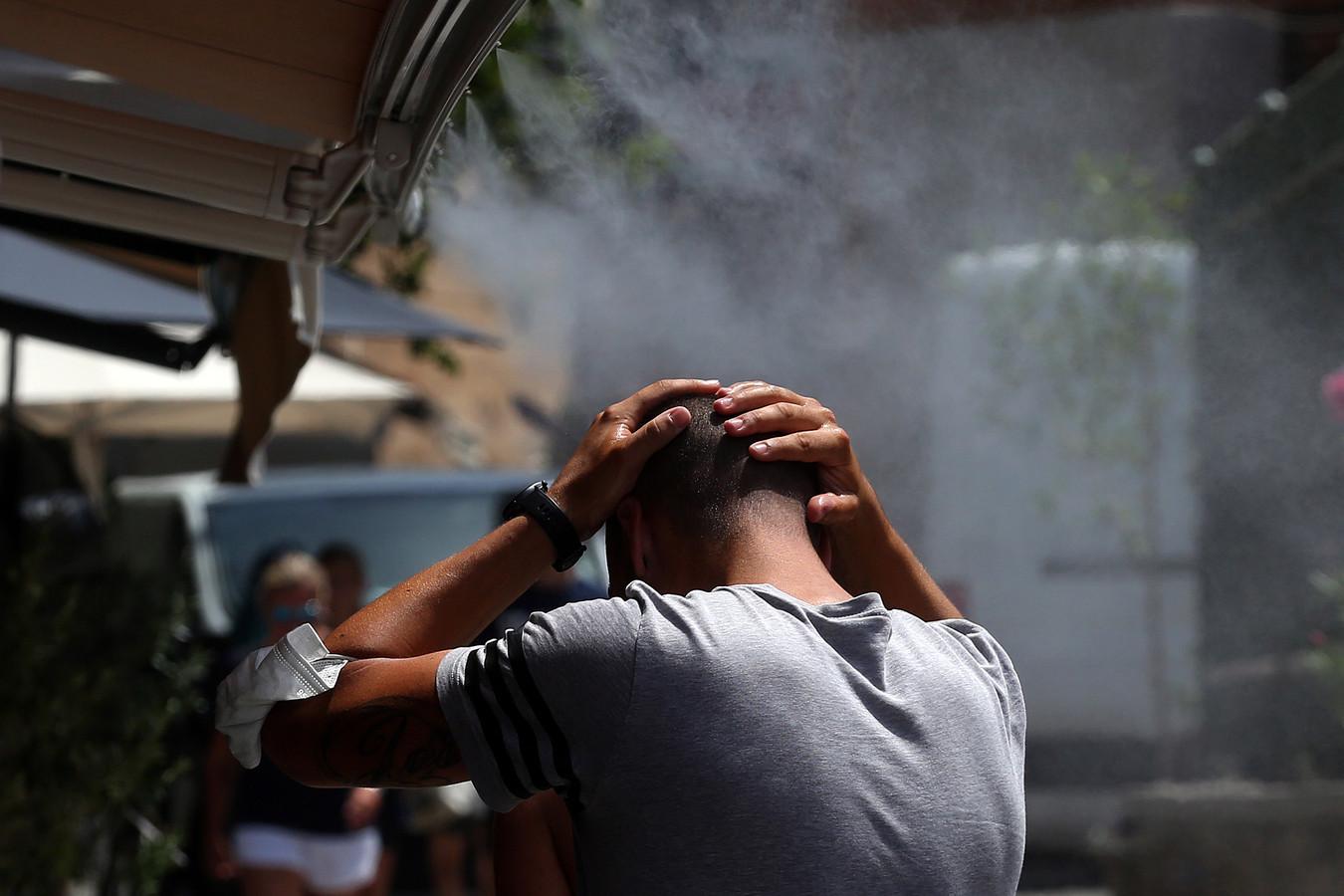 Een man koelt af onder een vernevelaar in Athene.