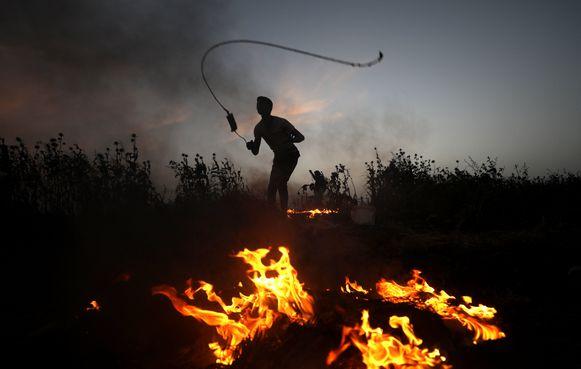 Palestijnse betoger gooit met stenen over het hek dat de grens tussen Gaza en Israël vormt.