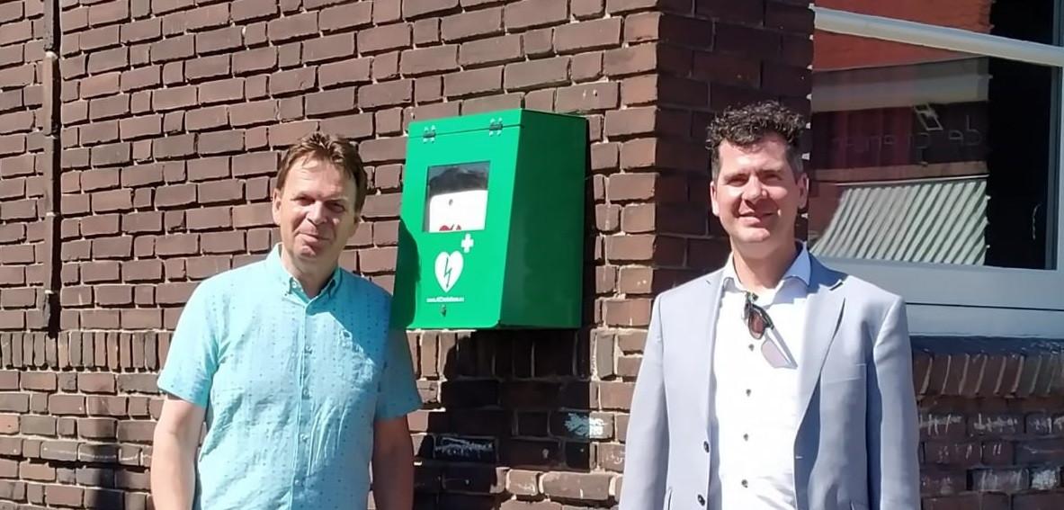 René Luijten (links) en wethouder Jurgen Vissers bij de nieuwe AED bij basisschool De Grienden in Lage Zwaluwe.