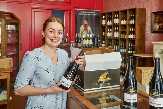 Joyce Muller pakt een doos met flessen van het Belgische wijndomein Ravenstein uit. Op de achtergrond een levensgroot portret van koning Lodewijk Napoleon.