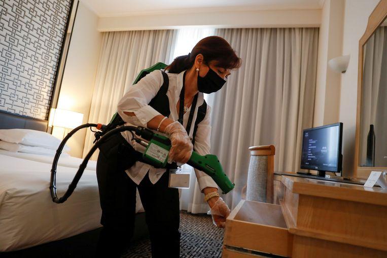 Een vrouw spuit desinfectiespray in een hotelkamer in Lissabon. Beeld Reuters