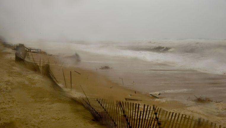 Een hek wordt weggeblazen aan de kust in de staat New York. Beeld AFP