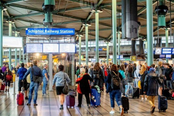 De aankomsthal van treinstation Schiphol waar trein- en luchtreizigers kriskras door elkaar lopen.