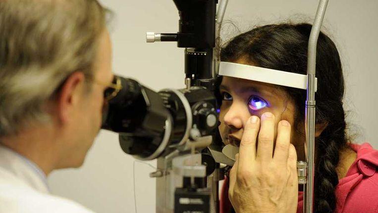 Oogarts Tjeerd de Faber onderzoekt tijdens de nieuwjaarsnacht in het Oogziekenhuis Amisha Sewlal (8) uit Rotterdam die vuurwerk in haar oog heeft gekregen Beeld anp