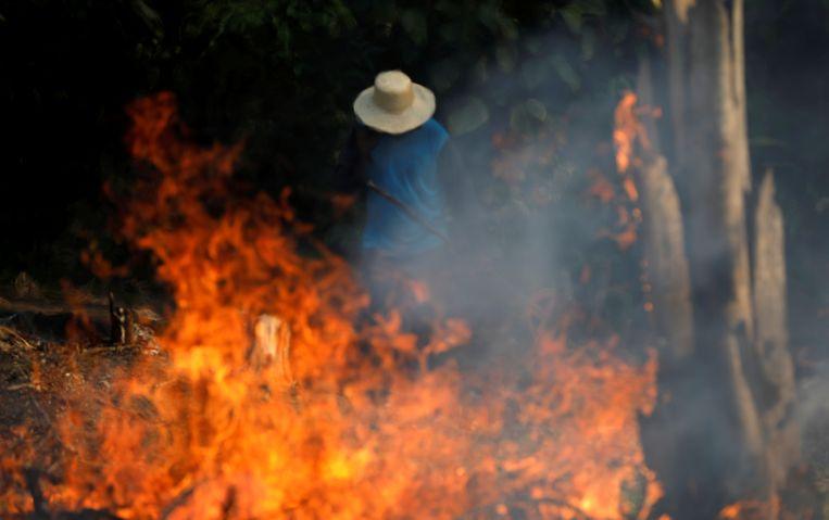 Een man aan het werk in een stuk van het Amazone-regenwoud dat met vuur brand wordt klaargemaakt voor landbouw. Beeld REUTERS