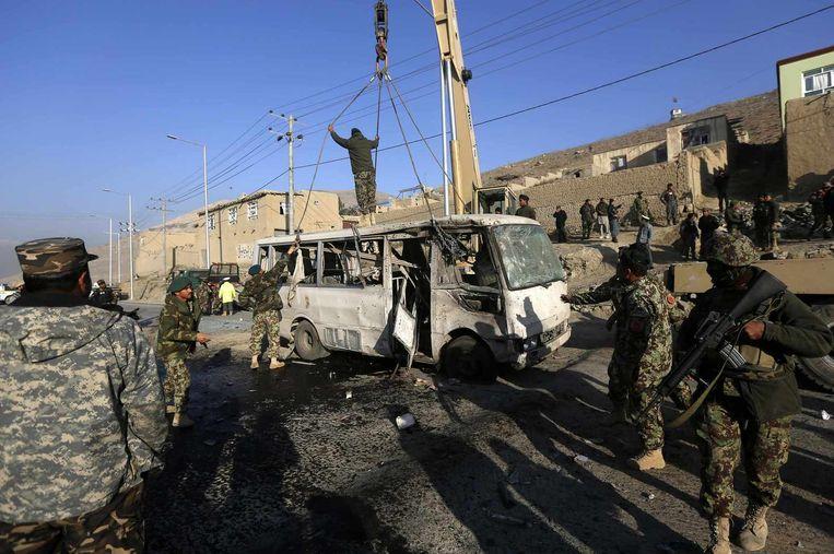 Afghaanse militairen verwijderen de bus die is getroffen door een zelfmoordaanslag.