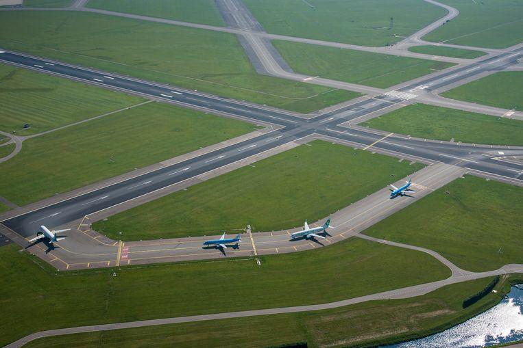 Vliegtuigen op Schiphol wachten op hun vertrek vanaf de Aalsmeerbaan. Beeld ANP