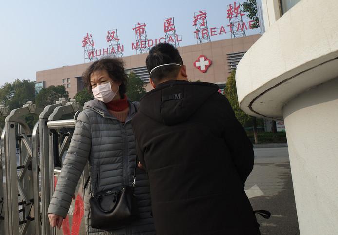 Chinezen bij een ziekenhuis in Wuhan beschermen zich tegen besmetting met het nieuwe coronavirus