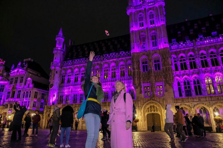 Els Ampe gooit een roze lintje op terwijl de gebouwen op Grote Markt roze kleuren.