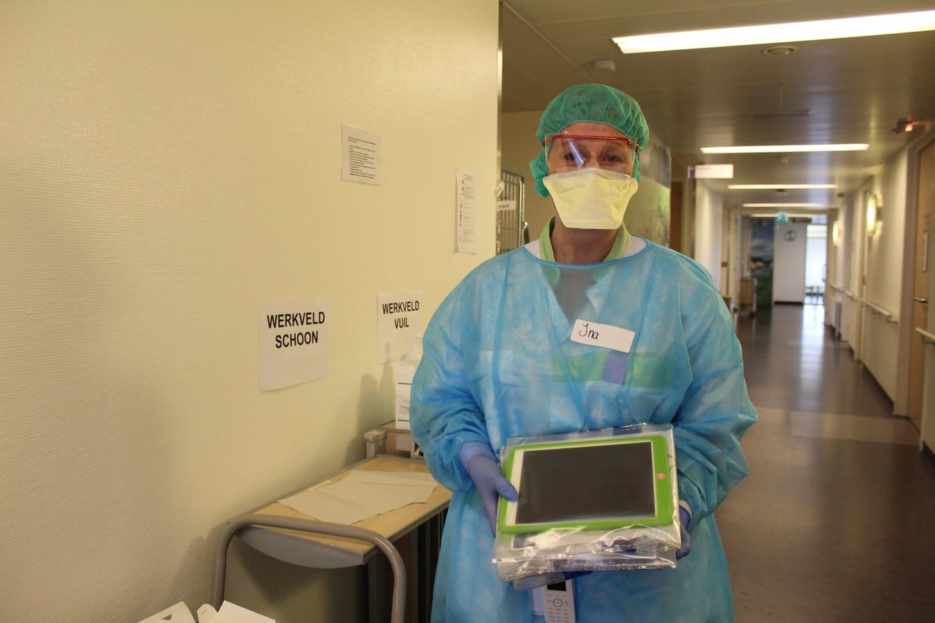 Een verpleegkundige op de corona-afdeling van het SKB in Winterswijk toont één van de iPad's (netjes ingepakt in een beschermhoesje) voor patiënten die in afzondering op de afdeling liggen. Foto ter illustratie.