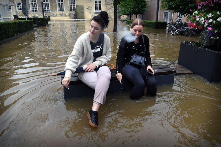 Zelfs in een overstroming nemen jongeren de tijd om een sigaretje te roken.  Beeld Marcel van den Bergh / de Volkskrant