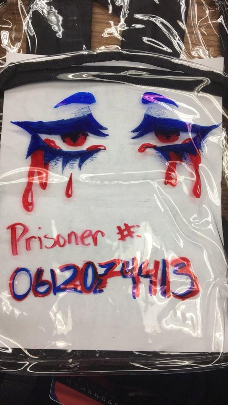 Een leerling versierde zijn doorzichtige rugzak met het woord 'prisoner', 'gevangene'. Beeld REUTERS
